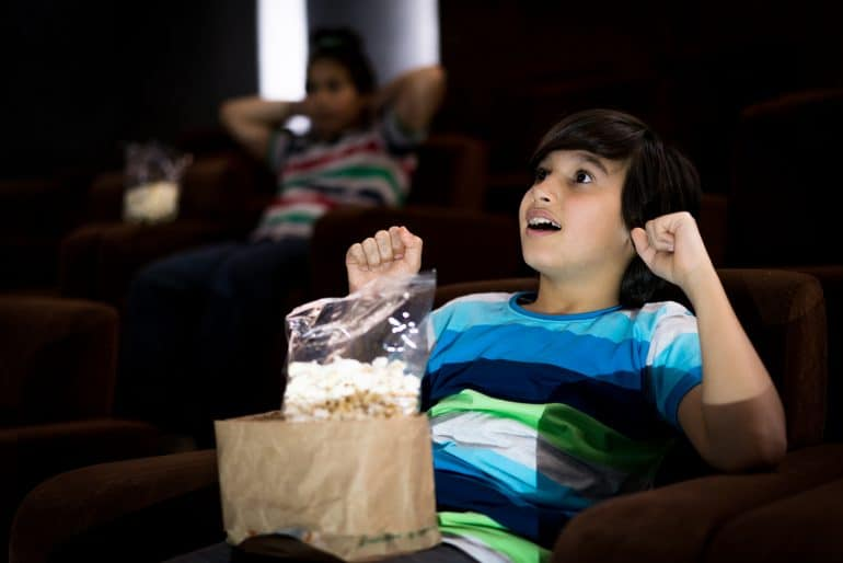 Child at the cinema watching movie